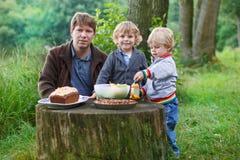 Pai novo e dois rapazes pequenos que tomam parte num piquenique no nea da floresta da natureza Foto de Stock Royalty Free