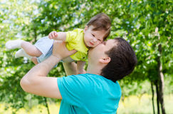 Pai novo e feliz que aumenta seu bebê Fotografia de Stock Royalty Free