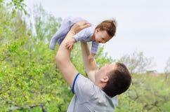 Pai novo e feliz que aumenta seu bebê Imagens de Stock Royalty Free