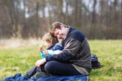 Pai novo e filho pequeno que têm o piquenique e o divertimento perto do la da floresta Foto de Stock Royalty Free