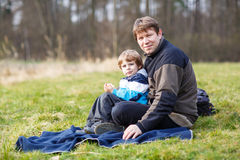Pai novo e filho pequeno que têm o piquenique e o divertimento perto do la da floresta Imagem de Stock Royalty Free