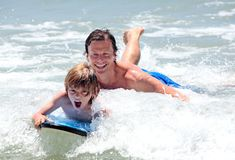 Pai novo e filho que aprendem surfar foto de stock