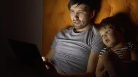 Pai novo e seu filme de observação dos desenhos animados do filho pequeno usando o tablet pc e falando ao encontrar-se na cama no Imagem de Stock Royalty Free