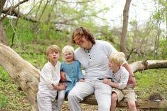 Pai novo e suas três crianças felizes que jogam e que riem O imagens de stock royalty free