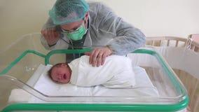 Pai novo emocional que acaricia a criança recém-nascida, sono do bebê na cama no hospital filme