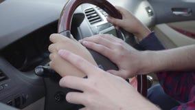 Pai novo irreconhecível que ensina seu filho conduzir acima o fim do carro O menino que senta-se nos regaços do pai, pondo vídeos de arquivo