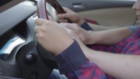Pai novo irreconhecível que ensina seu filho conduzir acima o fim do carro O menino que senta-se nos regaços do pai, pondo video estoque
