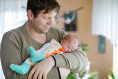 Pai novo orgulhoso feliz que guarda sua filha recém-nascida de sono do bebê Imagens de Stock Royalty Free