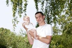 Pai novo orgulhoso que prende seu bebé Fotografia de Stock Royalty Free