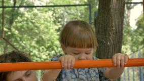 Pai novo que ajuda seu filho pequeno a escalar na escada no campo de jogos no parque, verão video estoque