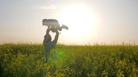 Pai novo que aumenta a criança acima em despesas gerais do ar na natureza, pai que engana com o filho no prado, paizinho feliz co filme