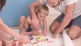 Pai novo que ensina ao seu o menino da criança como pintar Imagens de Stock