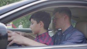 Pai novo que ensina seu filho conduzir acima o fim do carro O menino que senta-se nos regaços do pai, escutando ele A crian?a video estoque