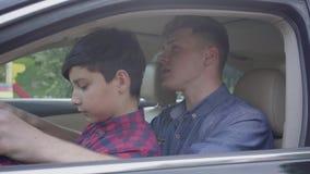 Pai novo que ensina seu filho conduzir acima o fim do carro O menino que senta-se nos regaços do pai, escutando ele A crian?a filme