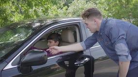 Pai novo que ensina seu filho conduzir a posição do carro perto do veículo O menino que senta-se no assento de motorista, escutan vídeos de arquivo