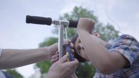 Pai novo que ensina seu filho fixar o close-up do 'trotinette' Opinião lateral o menino bonito com chave de fenda, tentando desap vídeos de arquivo