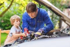Pai novo que ensina seu filho pequeno reparar o óleo de motor no fami foto de stock royalty free