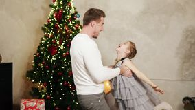 Pai novo que guarda as mãos de sua filha e que gira a ao redor em casa pela árvore de Natal filme