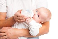 Pai novo que guarda e que alimenta seu bebê Fotos de Stock