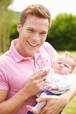Pai orgulhoso Holding Baby Daughter no jardim Imagem de Stock