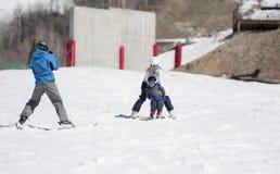 Pai Photographs Toddler Son como a mamã & a criança Ski Downhill fotografia de stock royalty free