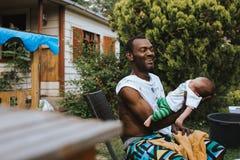 Pai preto que guarda e que ri de seu filho recém-nascido foto de stock