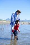 Pai que ajuda o filho deficiente a andar em ondas de oceano imagem de stock