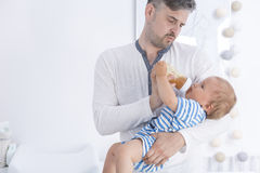 Pai que alimenta seu bebê imagem de stock royalty free