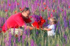 Pai que apresenta flores à filha Imagens de Stock