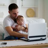 Pai que babysitting e que trabalha no computador foto de stock