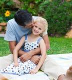 Pai que beija sua filha em um jardim foto de stock