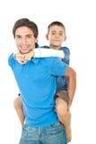 Pai que dá às cavalitas a seu filho imagens de stock