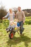 Pai que dá a crianças o passeio no Wheelbarrow Imagens de Stock Royalty Free
