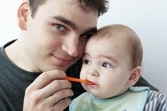 Pai que dá o alimento ao bebê Imagem de Stock