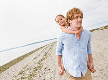 Pai que dá o passeio do sobreposto da filha na praia Imagem de Stock