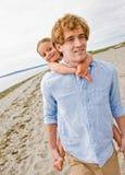 Pai que dá o passeio do sobreposto da filha na praia Imagens de Stock