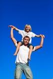 Pai que dá a seu filho um passeio do sobreposto Fotografia de Stock