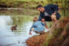 Pai que ensina a pesca pequena do filho na lagoa fotografia de stock royalty free