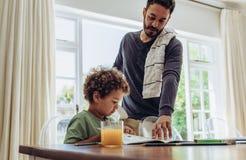Pai que faz seu filho fazer seu trabalho da casa da escola foto de stock royalty free