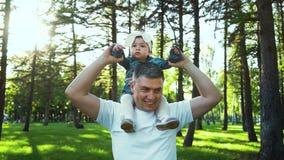Pai que gerencie ao redor sua filha da criança em ombros no jardim ensolarado vídeos de arquivo