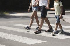 Pai que guarda as mãos com suas crianças quando no cruzamento pedestre fotografia de stock