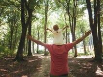 Pai que guarda a filha da menina em seu ombro As mãos espalharam largamente foto de stock royalty free