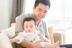 Pai que guarda o bebê que senta-se no sofá fotografia de stock