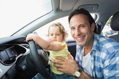 Pai que joga com o bebê no assento de motoristas fotografia de stock royalty free