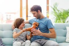 Pai que joga com seu filho no sof? imagem de stock royalty free