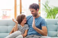 Pai que joga com seu filho no sof? imagem de stock