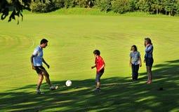 Pai que joga o futebol com crianças Imagens de Stock