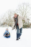 Pai que puxa o filho no Sledge através da neve Fotos de Stock
