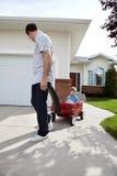 Pai que puxa o filho que senta-se no vagão Fotografia de Stock Royalty Free