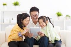 pai que usa o PC da tabuleta com meninas foto de stock